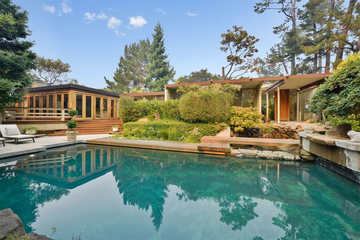 A swimming pool set in front of low-roofed post-and-beam home with floor-to-ceiling windows.