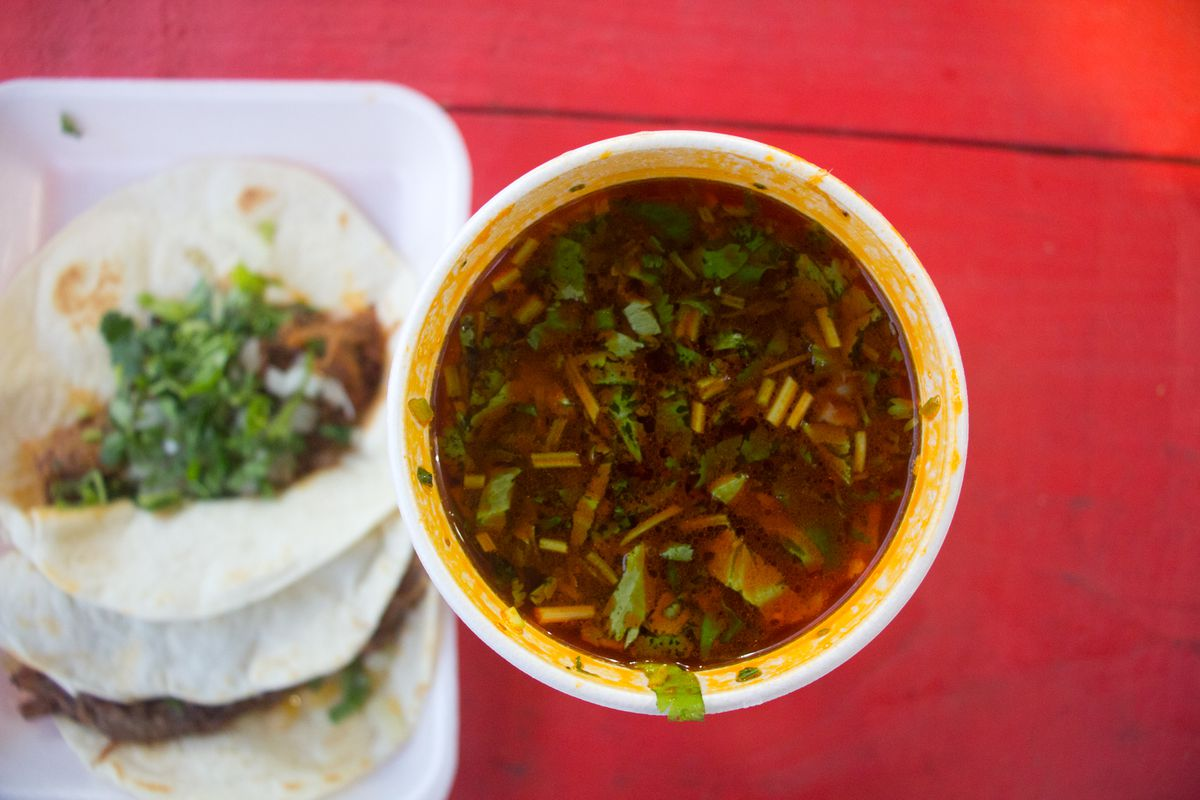 An overhead shot of a styrofoam cup of  consomme next to an out-of-focus styrofoam to-go container of two meat tacos topped with cilantro and onions on the left, all on a red table