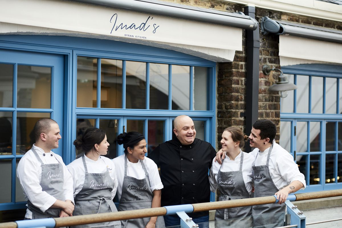 """A photo of restaurateur Imad Alarnab with a group of chefs in traditional whites, outside the entrance of a restaurant with blue windows and white signage that says """"Imad's Syrian Kitchen"""""""