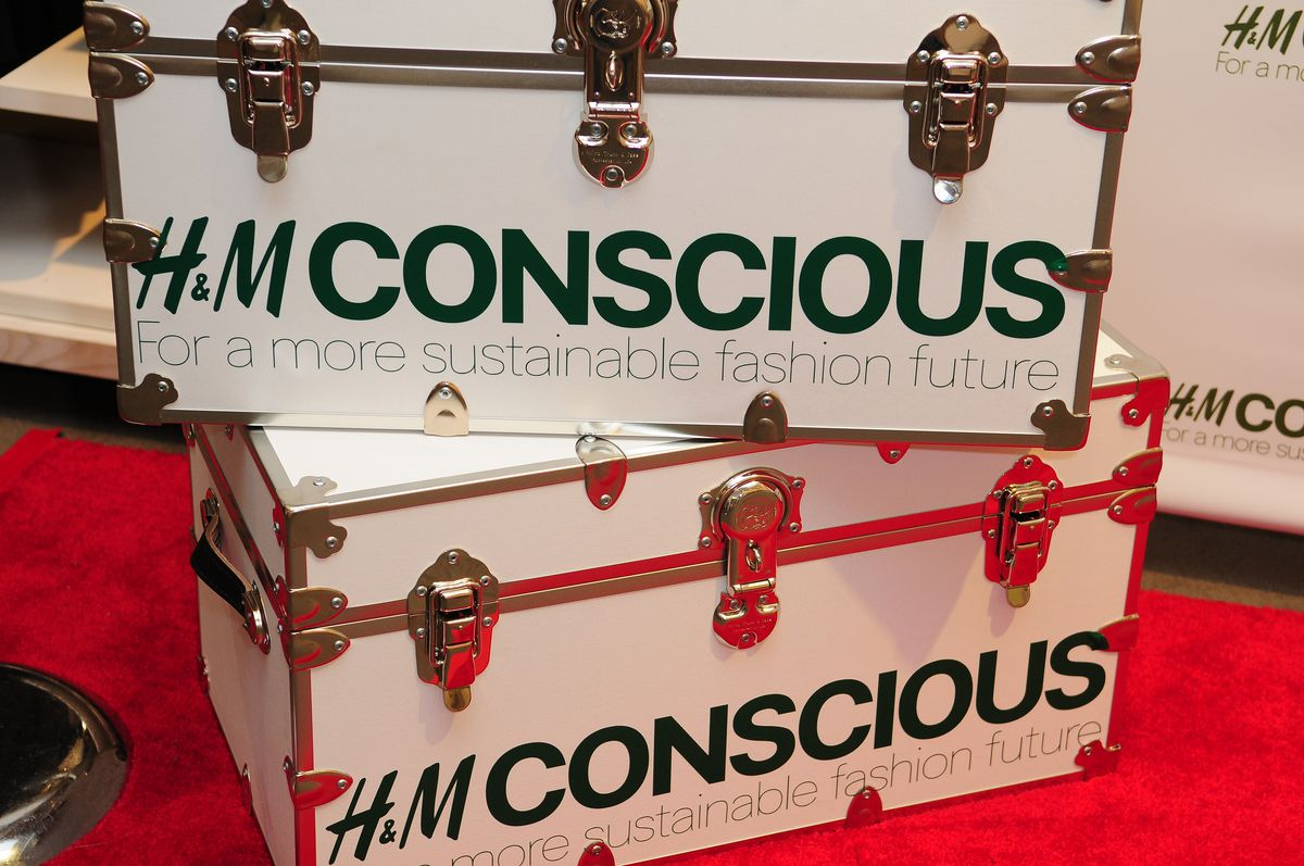 Suitcases displaying the logo of H&M's Conscious Collection at an event in Miami, Florida.