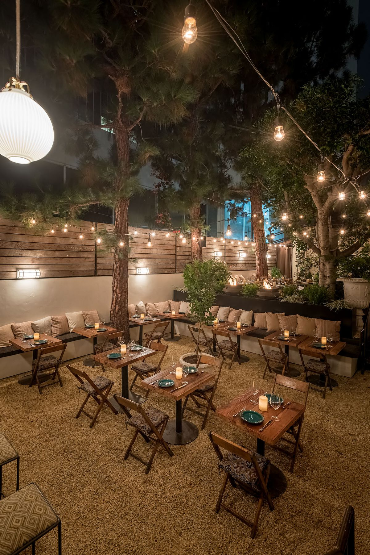 A tall shot of tables under a big tree out on a dinner patio at night.