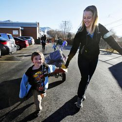 Zech Andrus and volunteer Sarah Borden bring bags of gifts to the Andrus family's car during the 2014 Operation Chimney Drop at Head Start in Salt Lake City, Monday, Dec. 15, 2014.