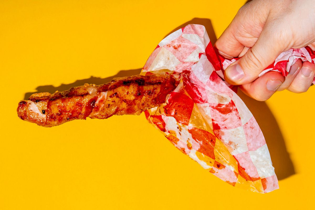 A hand holding a bacon-wrapped riblet on a stick against a yellow background
