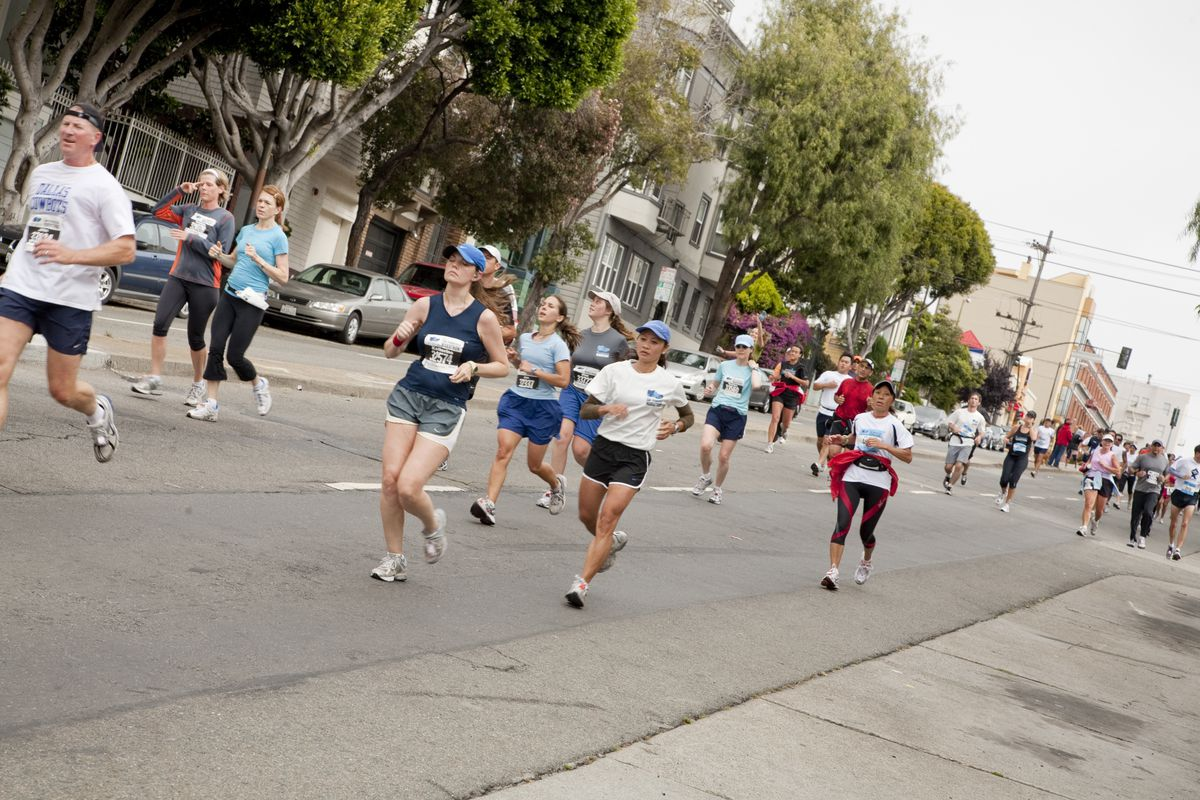 People running in the SF marathon on a street lined with trees.
