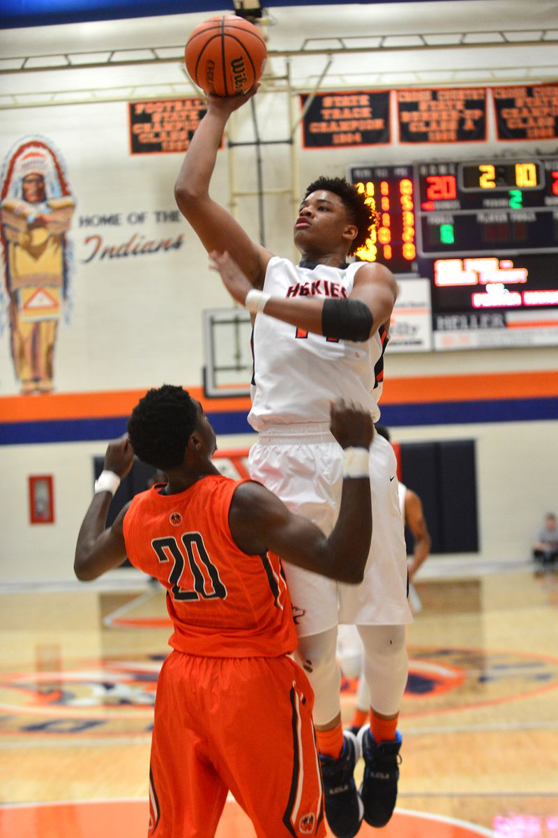 Oak Park's Cameron Gross (14) leaps to shoot over Peoria Manual's Da'Monte Williams (20) in 2015.