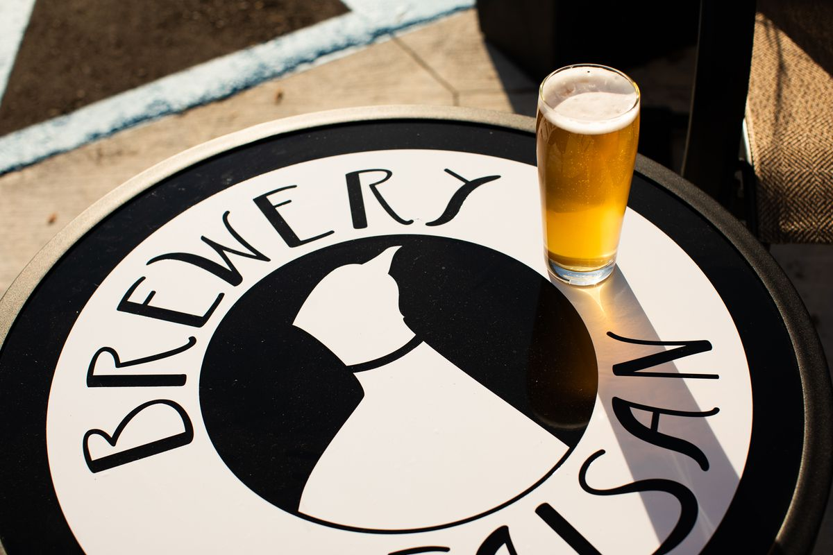 A witbier in a pint glass sits on a patio table emblazoned with a black and white Brewery Faisan decal with a pheasant on a sunny day.