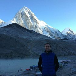 Steve Pearson stands for a photo with a peak named Pumori looming in the background. Mount Everest is a short distance away.
