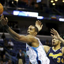 New Orleans Hornets guard forward Trevor Ariza (1) reaches for a loose ball as Denver Nuggets' JaVale McGee (34) defends during the first half of an NBA basketball game, Wednesday, April 4, 2012, in New Orleans.