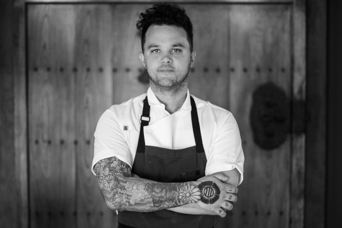 A black and white photo of Canlis chef Brady Williams with his arms folded
