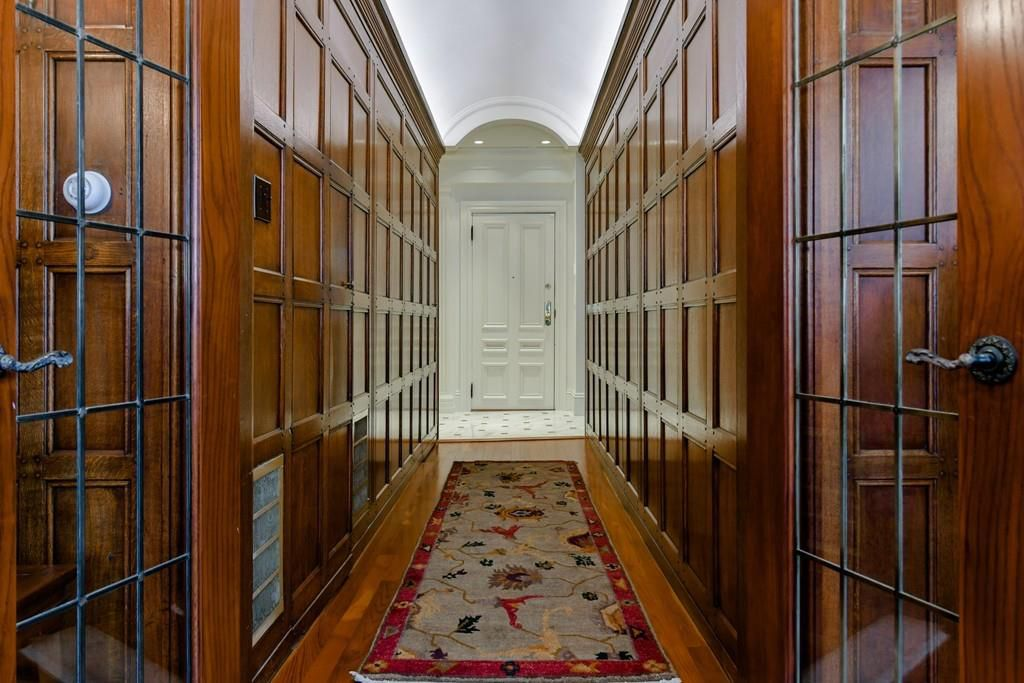 A long hallway with wood paneling on either side.