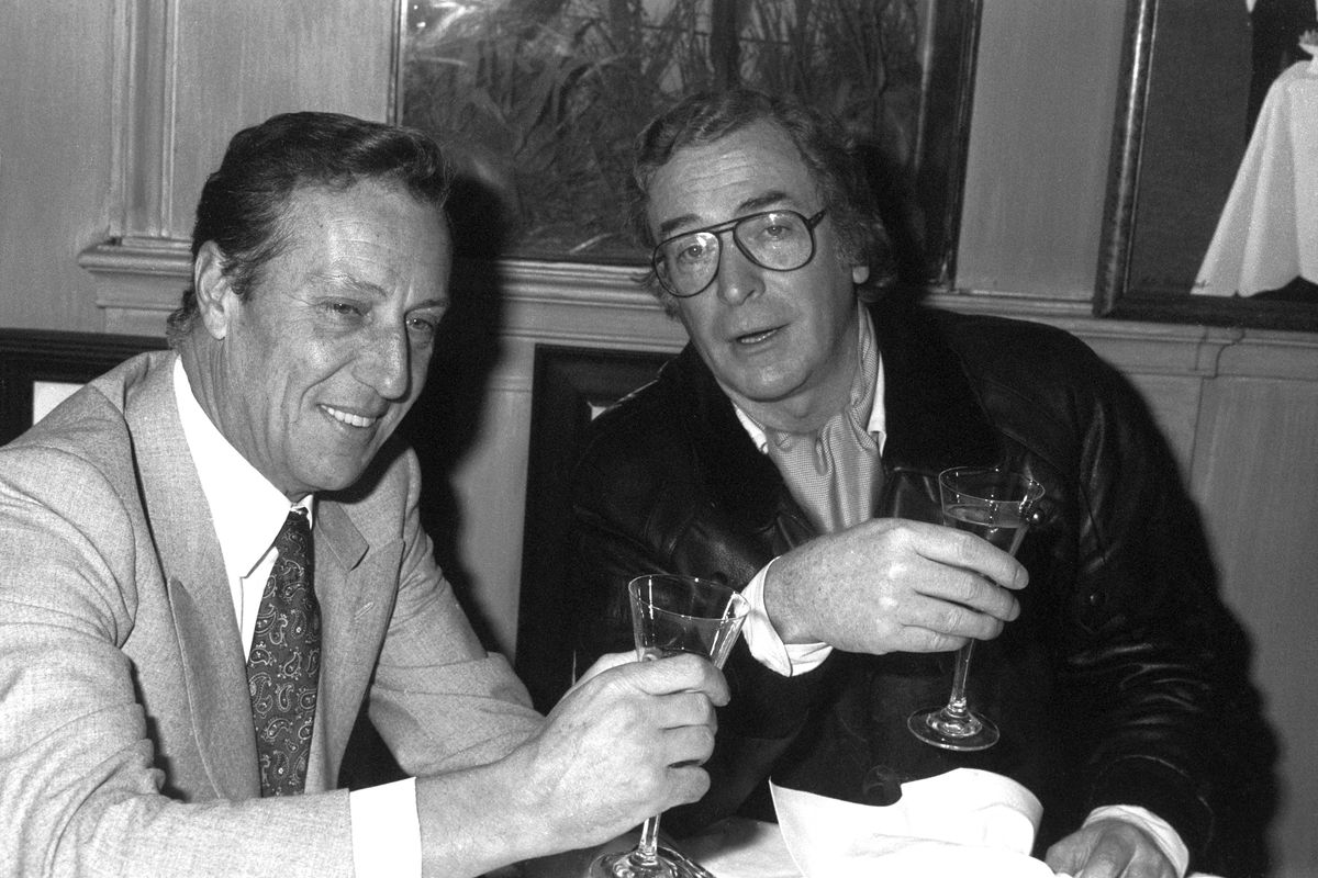 Michael Caine and Frederick Forsyth sit, wearing suits, inside Langan's Brasserie, drinking from champagne flutes