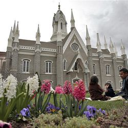 Visitors from California Kassabdra, 4, left, and Joaquin Ramirez munch a snack with their father, Raul, on the lawn near the Assembly Hall on Temple Square during the Saturday morning session of general conference.