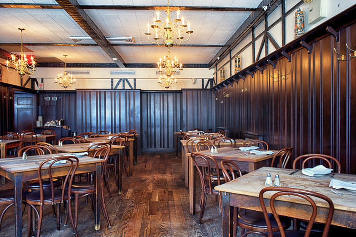 Peter Luger's dining room with chandeliers and multiple tables set for service.