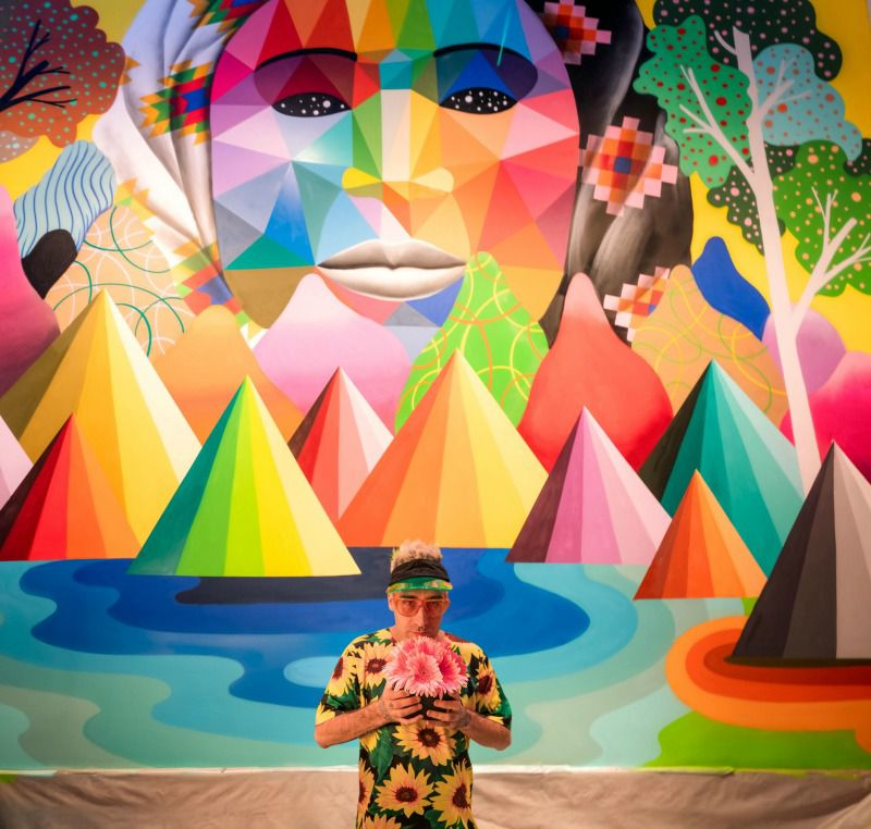 A man holds a bouquet of flowers in front of a mural inside Mama Rabbit