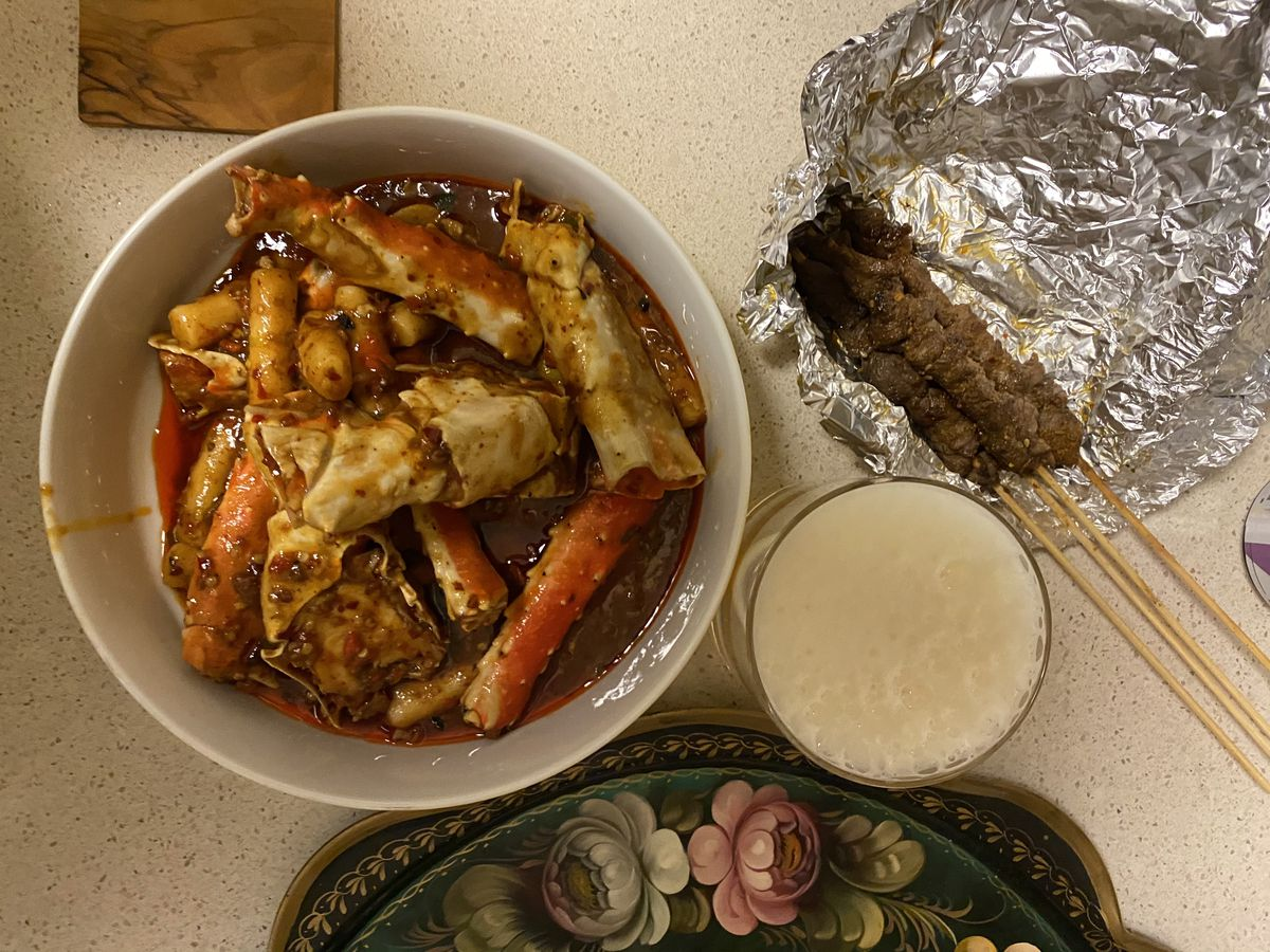 King crab sits in a chile broth n a white bowl above a white speckled countertop; lamb skewers sit above foil to the side, just above a glass of beer and a decorative Russian platter