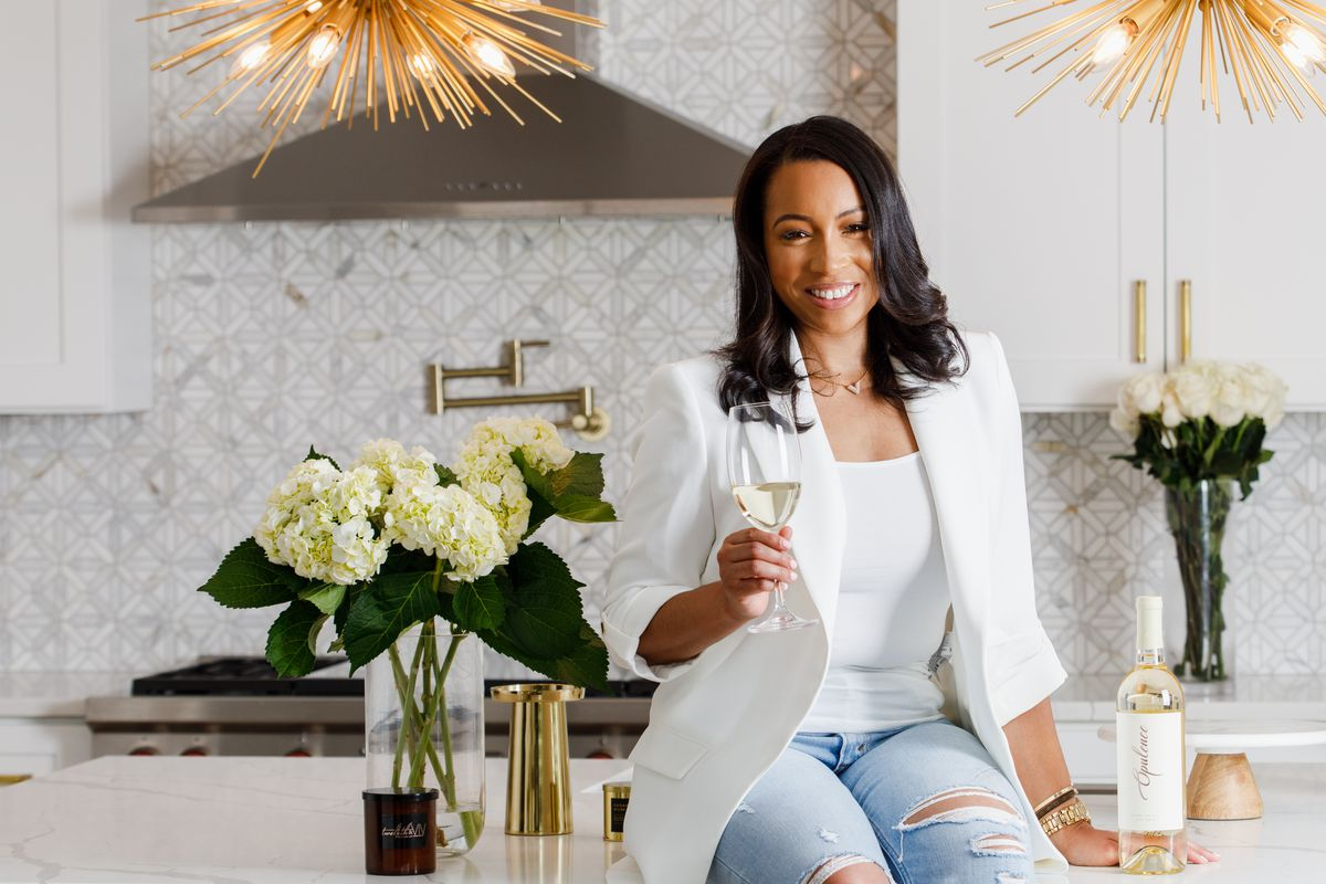 A woman sits on a kitchen granite counter holding up a wine glass