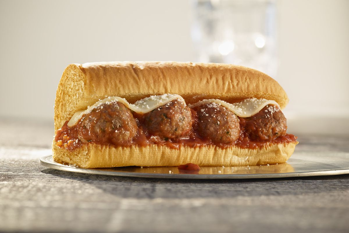A subway sandwich with four plant-based meatballs, covered in marinara sauce and mozzarella.