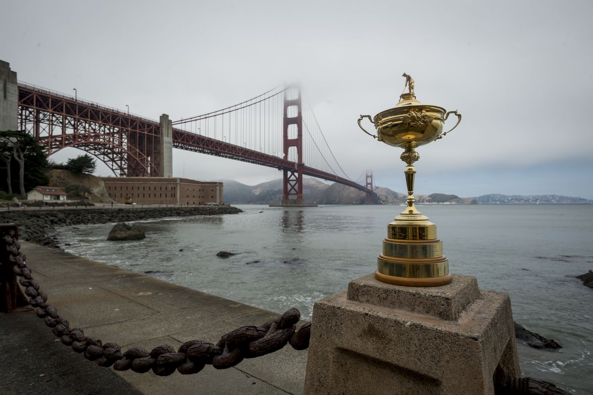 The Golden Gate Bridge in San Francisco, with a golden trophy in the foreground.
