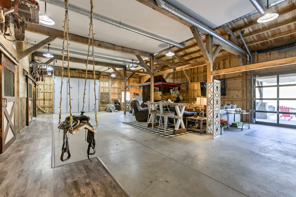 An interior view of the lower level of a barn house, with an open garage feel, small living room, and hanging saddle.