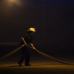 A firefighter struggles with the hose alone at 59th Street and 11th Avenue as several businesses burn nearby, including the Wisconsin Department of Corrections' Community Corrections Division, in the second night of unrest after police shot Jacob Blake, Monday night, Aug. 24, 2020.