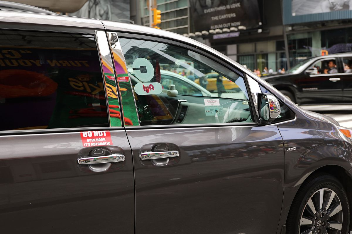 A black car with the Uber and Lyft logos drives around NYC.
