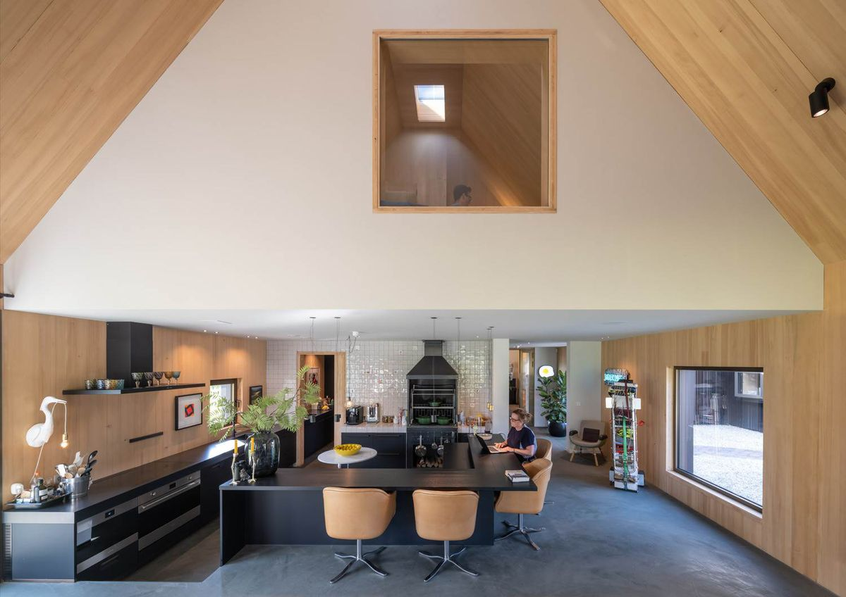 A living room with a gabled, wooden ceiling. A kitchen and L-shaped island is on the main floor, and a square window can be seen upstairs.