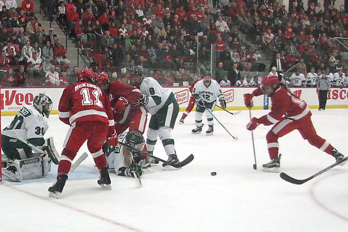 Wisconsin's Sarah Nurse tries to get the puck through the scrum in front of the Dartmouth goal.