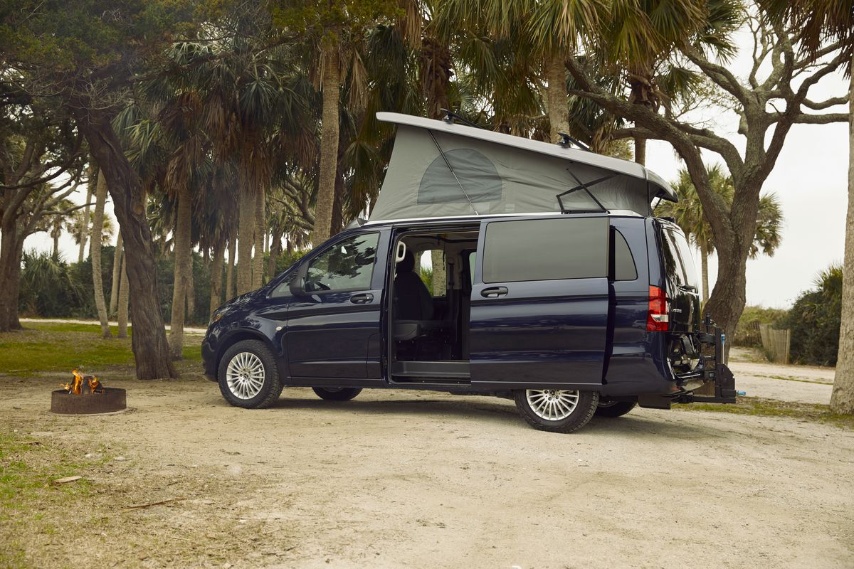 A side view of the pop-top camper van with the side door open and the roof popped up.