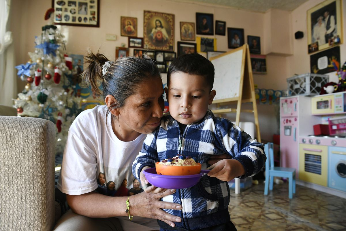 Olga Montellano, an informal child care provider, says goodbye to Mateo Casillas, 2, after caring for him for the day.