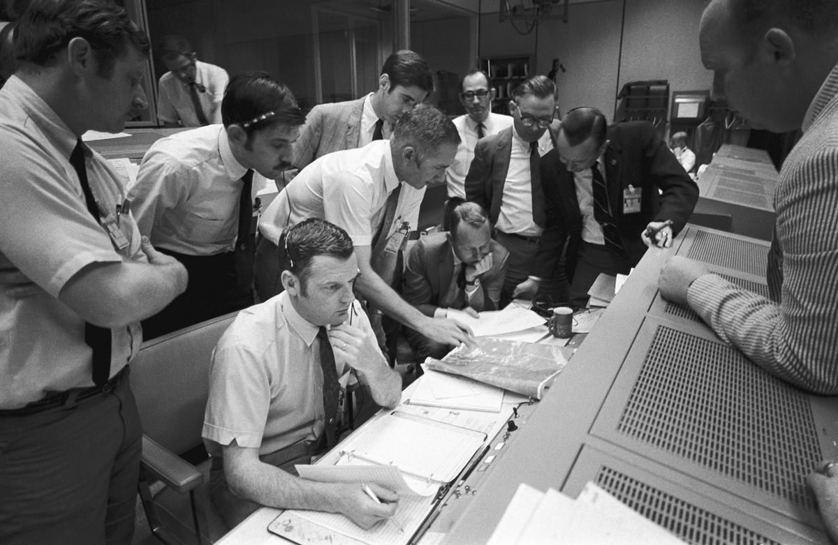 In this April 15, 1970 photo made available by NASA, a group of flight controllers gather around the console of Glenn S. Lunney (foreground, seated), Shift 4 flight director, in the Mission Operations Control Room of Mission Control Center in Houston. Their attention is drawn to a weather map of the proposed Apollo 13 landing site in the Pacific Ocean.
