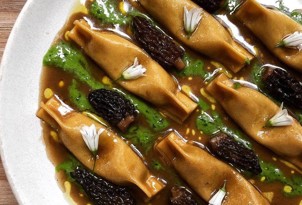 A plate of stuffed pasta in a borwn sauce with a drizzled green sauce and morel mushrooms