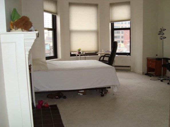 A studio apartment with a bed and an office chair as well as an ornamental fireplace.
