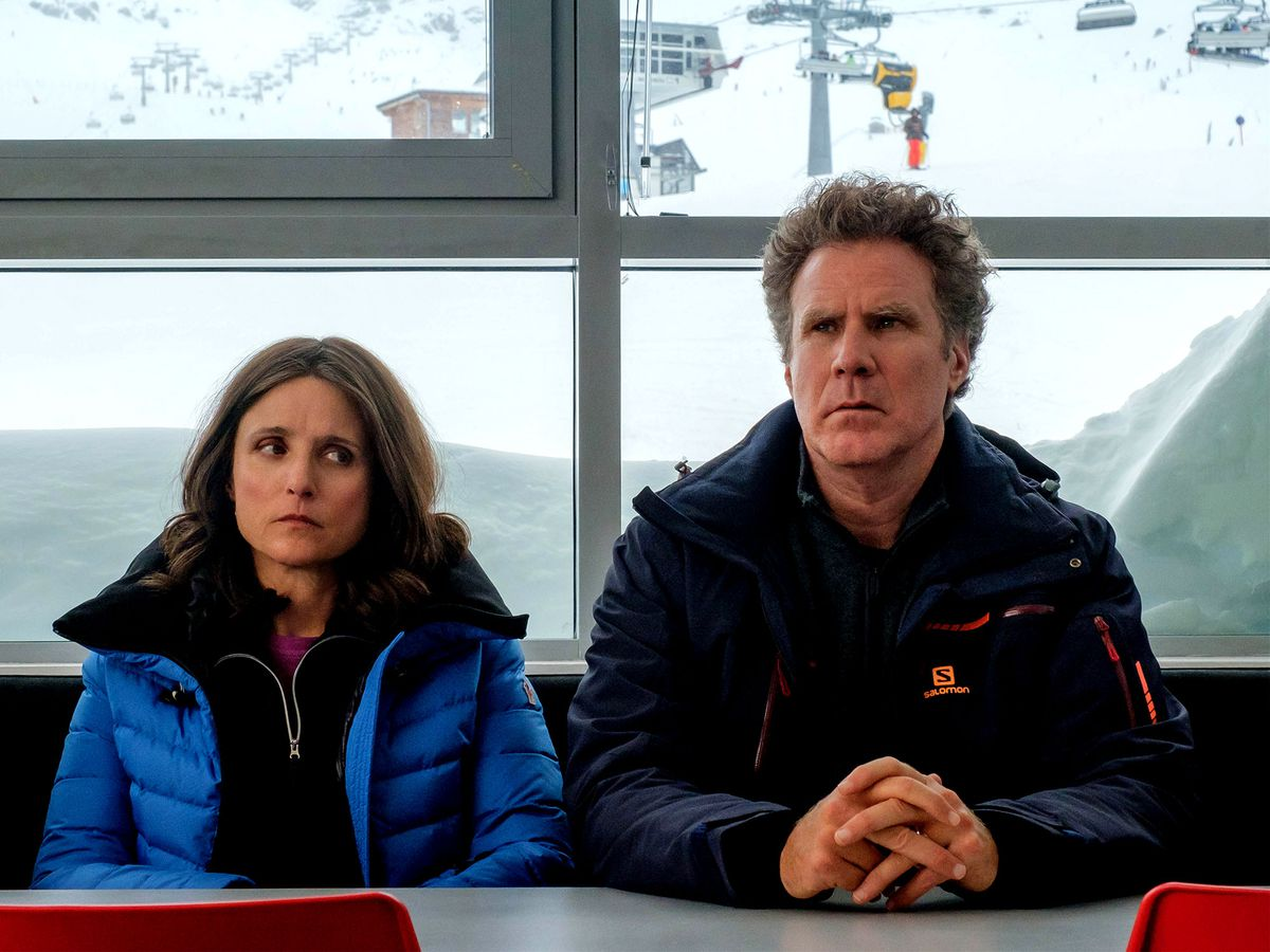 a couple sit next to each other, looking unsure, with a snowy mountain behind them in Downhill
