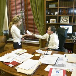 Gov. Gary Herbert talks to his personal assistant Ashlee Buchholz Wednesday.