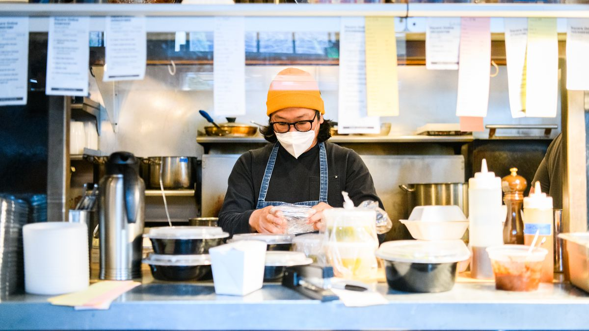 A chef in a yellow beanie and white KN95 mask works from behind the chef's pass in the kitchen at Toki