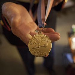 Eighty-seven-year-old retired Marine John Cole, who served and was wounded in North Korea, shows one of his medals at his home in Roy Wednesday, Feb. 18, 2015.