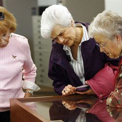 From left, RoseMarie Breinholt, Marion Stoff and Ruth Petersen look at a World War II prisoner photo in the an exhibit at the LDS Church History Library on Friday.