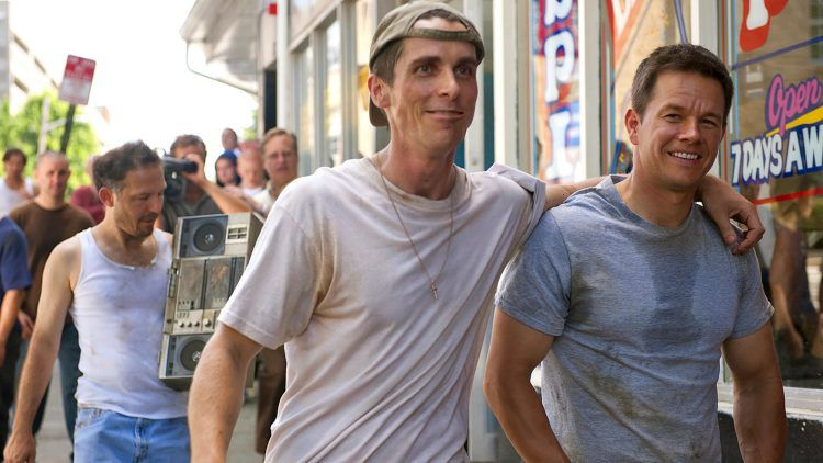 Dicky (Christian Bale) drapes his arm over his brother Micky's (Mark Wahlberg) shoulder in The Fighter