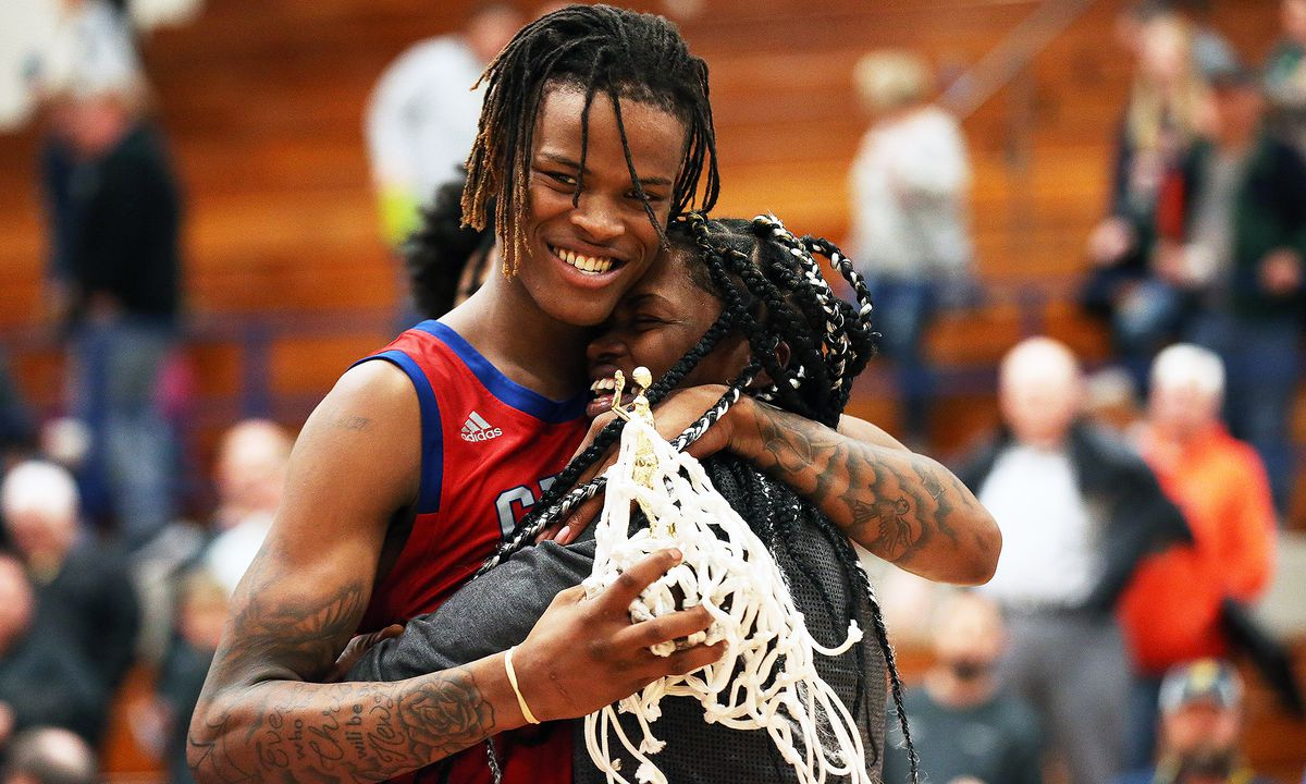 Curie's Ramean Hinton hugs his mom after the Condors win the Pontiac Holiday Tournament and he was named the A.C. Williamson award winner.
