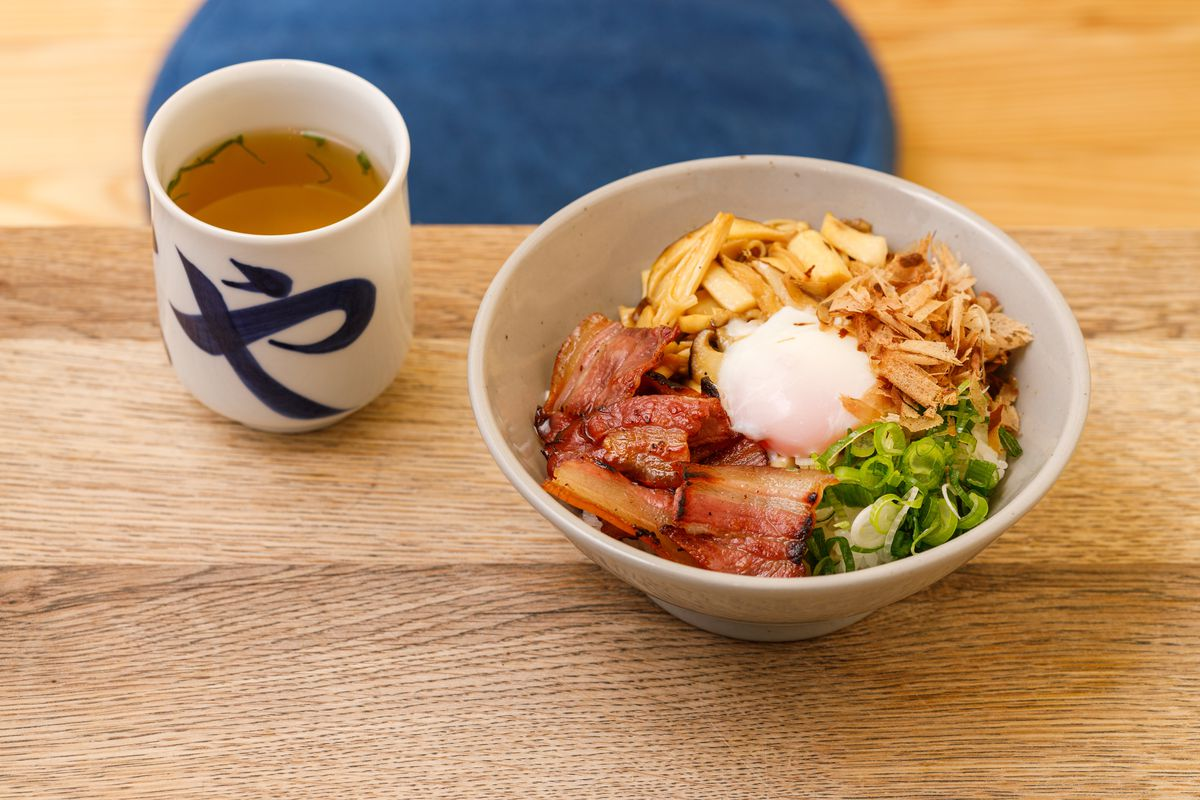 A bowl of udon noodles with raw egg, bacon, spring onion, and mushroom, with a cup of dashijoyu on the side