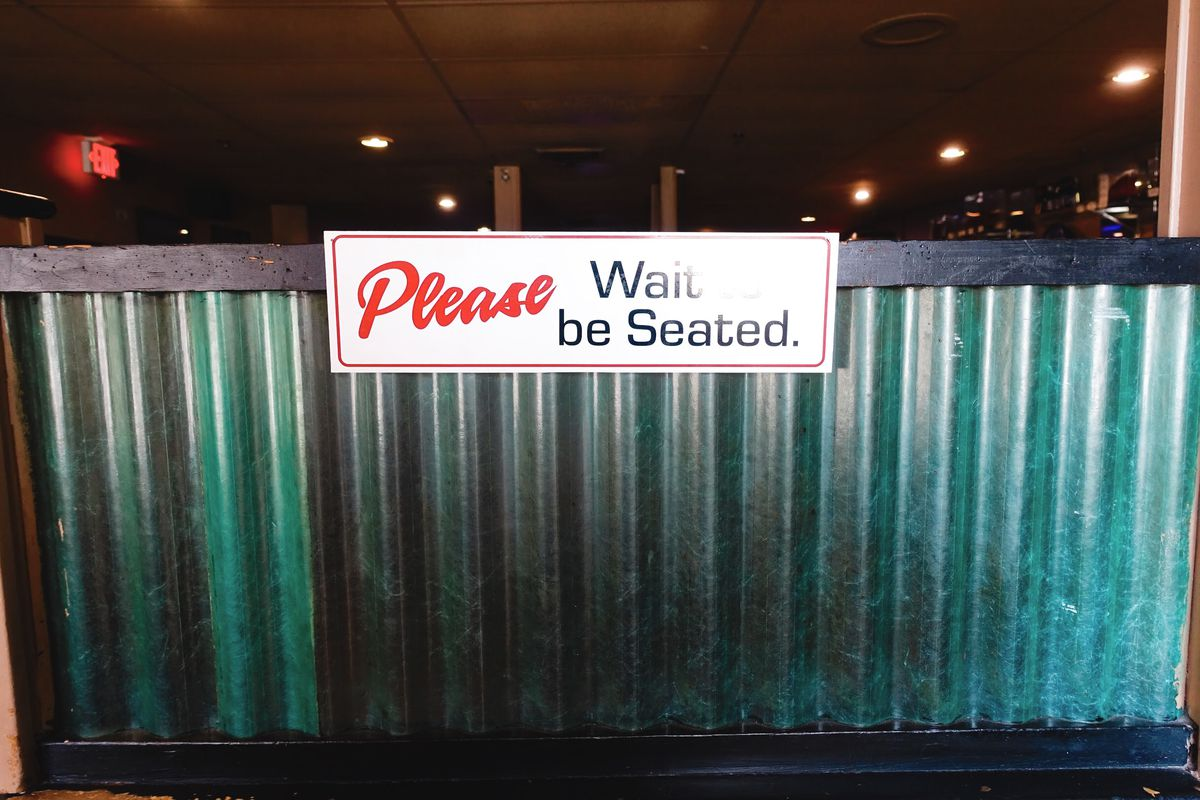 """A """"please wait to be seated"""" sign at Santarpio's"""