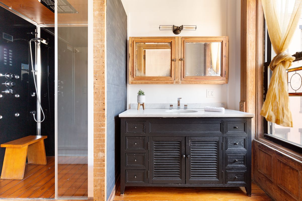 A black vanity with two square mirrors hanging above.