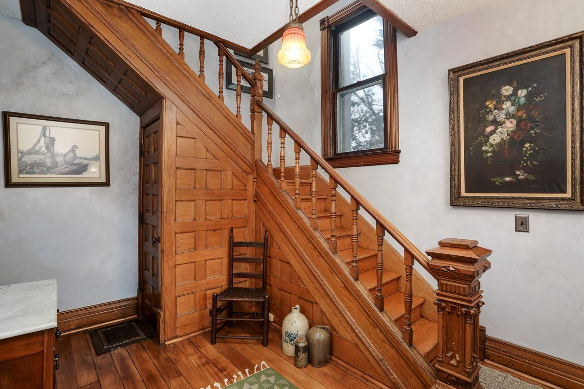 A view of the staircase with a tiny room underneath. There's also hardwood floors and a still-life painting of flowers.