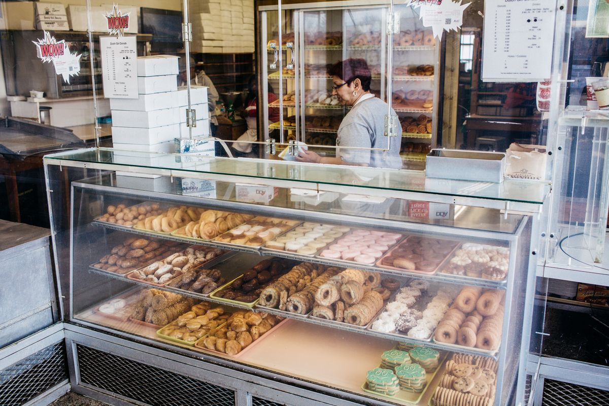 A woman in an apron walks behind the doughnut counter surrounded by bullet-proof glass.
