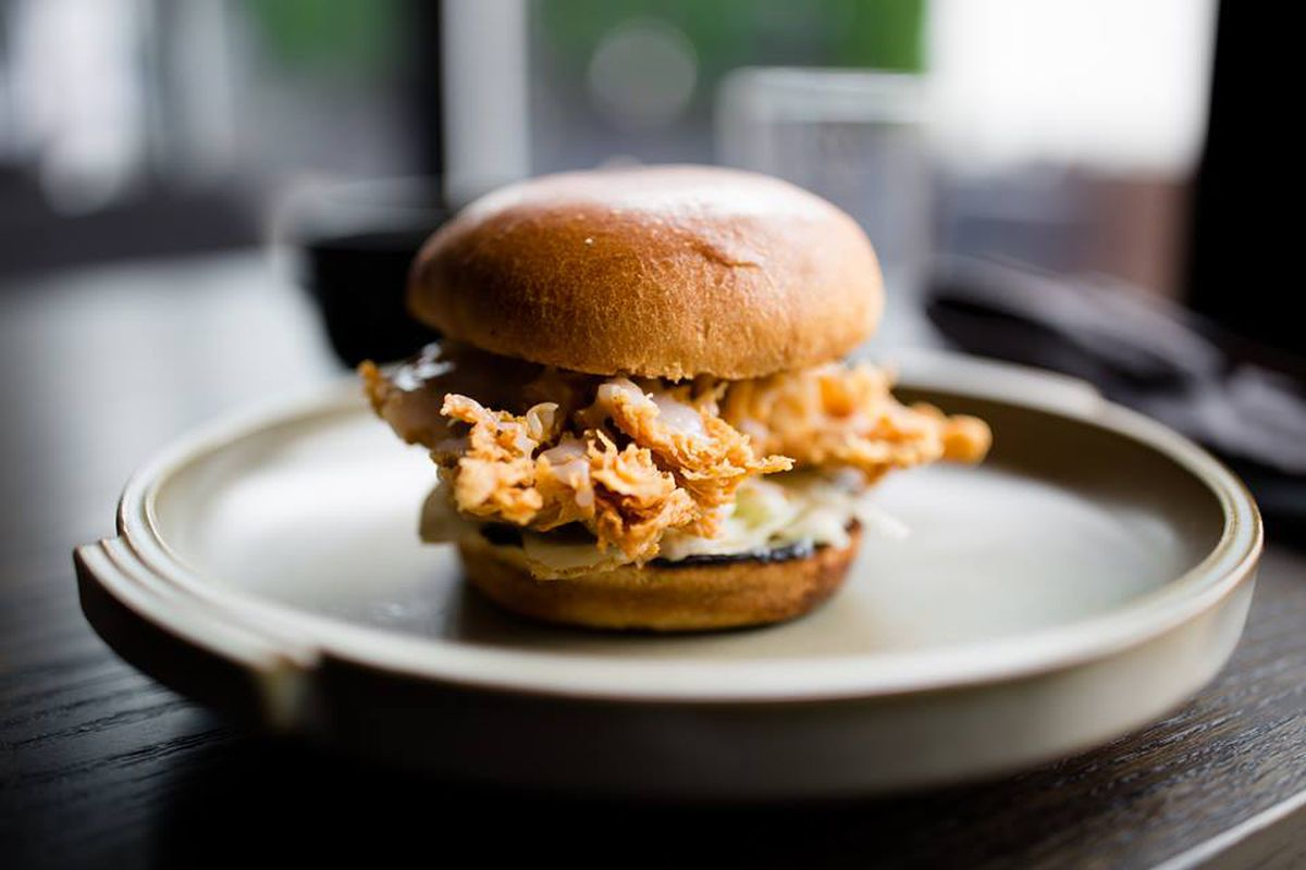 A fried chicken sandwich on a bun on a round plate.