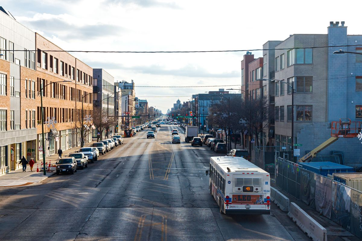 A bus travels down Western Avenue. There are apartment buildings on either side of the four lane road.