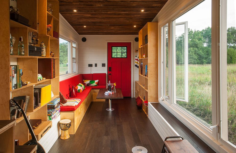The interior of a tiny home. There are bookshelves with various objects and books on the shelves. There is a couch, table, and counters. There are large windows looking out onto a field.