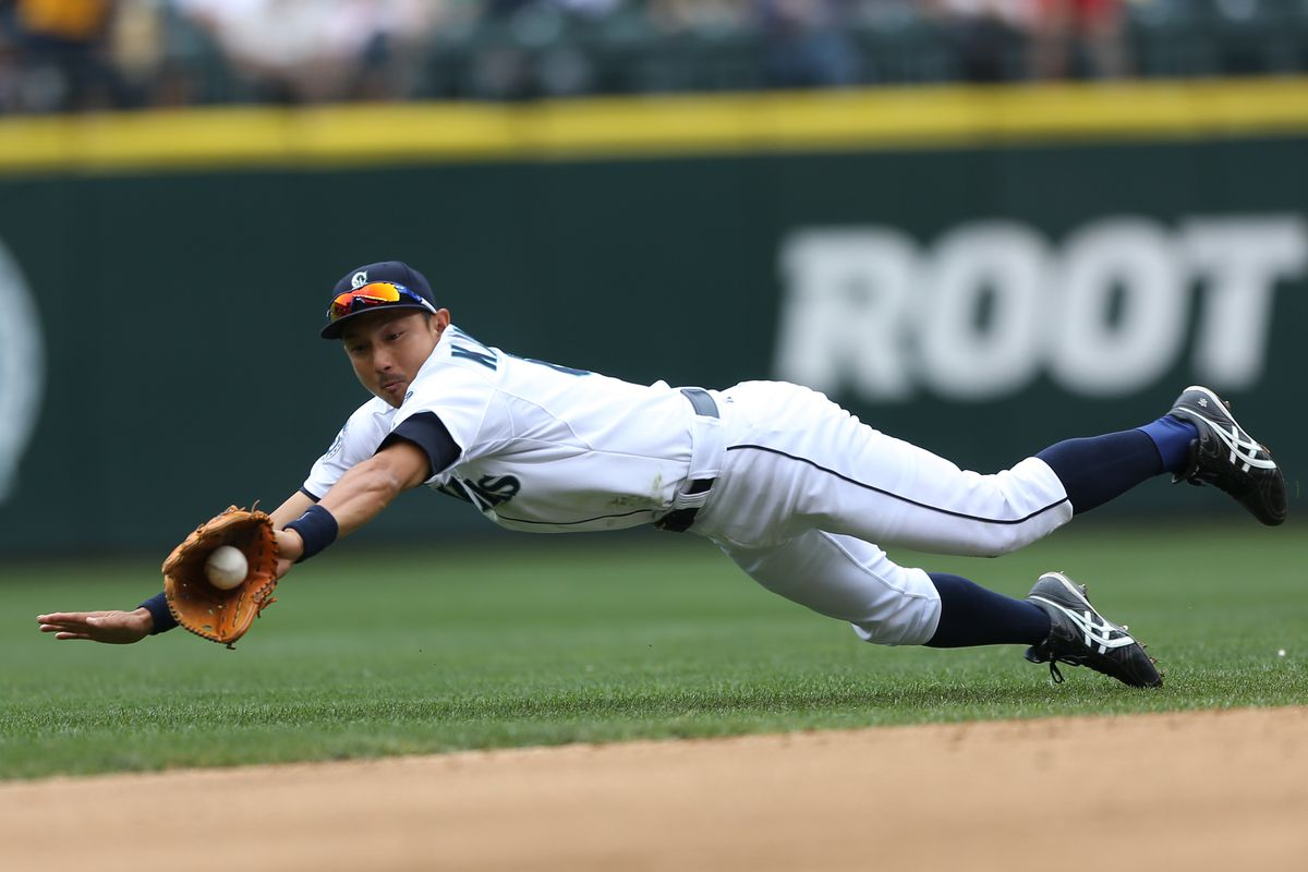 SEATTLE, WA - AUGUST 19:  Munenori Kawasaki #61 of the Seattle Mariners dives for a single by Justin Morneau of the Minnesota Twins at Safeco Field on August 19, 2012 in Seattle, Washington.  (Photo by Otto Greule Jr/Getty Images)