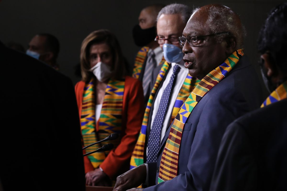 Rep. Jim Clyburn, in a dark suit and a kente cloth stole, speaks into a microphone; behind him are Nancy Pelosi in a red suit and Chuck Schumer in a blue suit — both masked and also wearing kente cloth stoles.