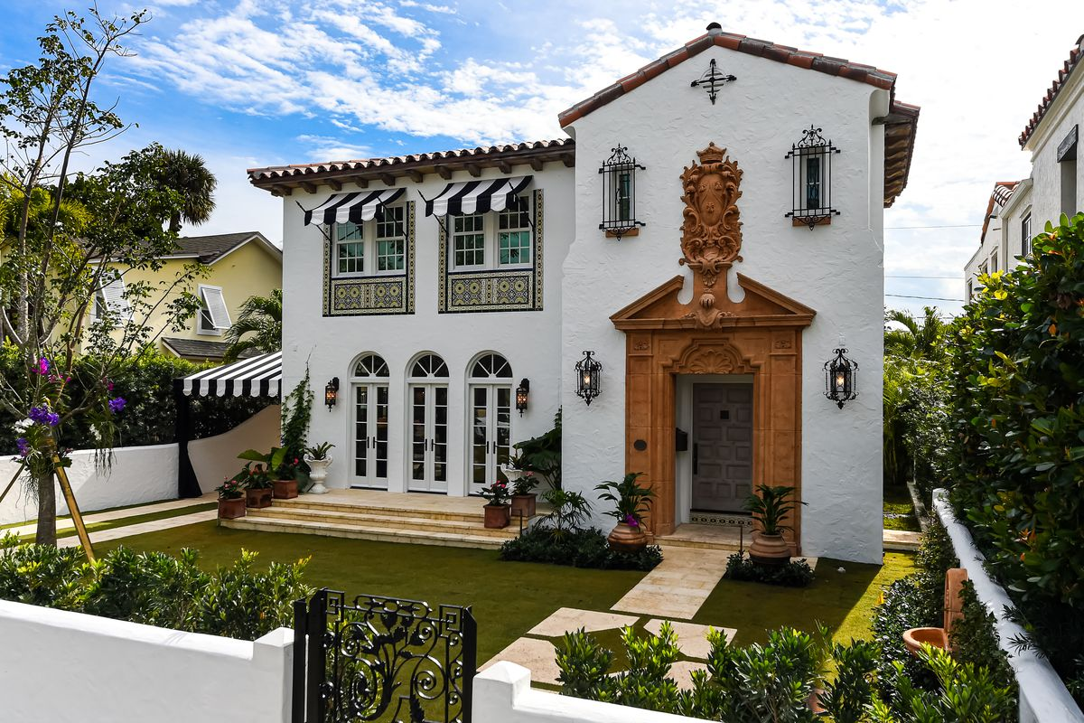 A Spanish style home features white stucco, striped awnings, and an elaborate wood portico at the entrance.